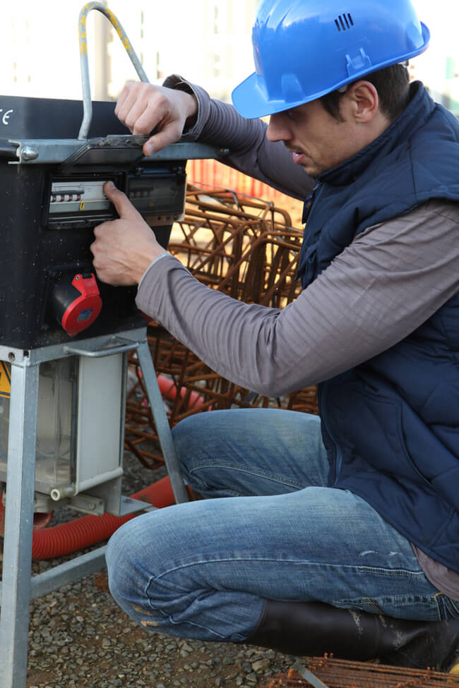 Man looks at a portable generator to ensure his power solutions can provide temporary power for his construction site.