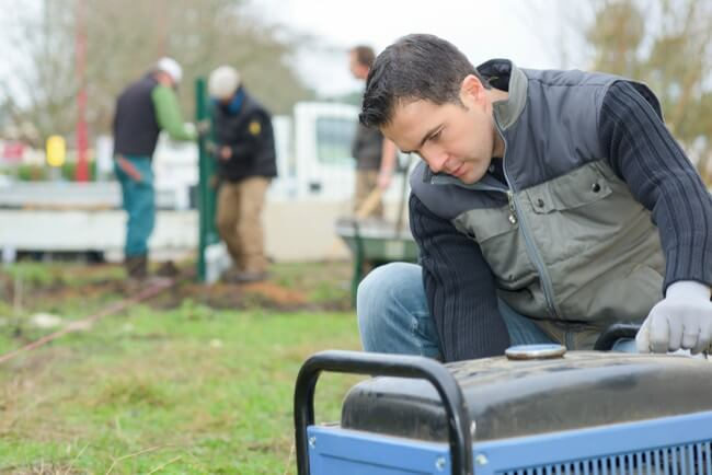 Man checks a portable generator to prepare his temporary power for a power outage.