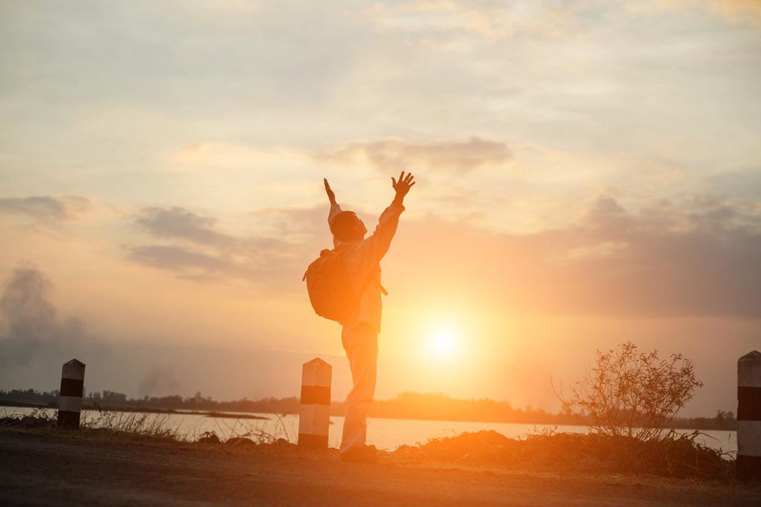 guy standing in front of sunset with his hands up to the sky